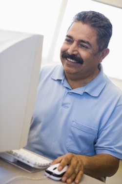 Mature Hispanic Man working at computer
