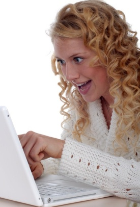 Blonde woman excitedly working at computer